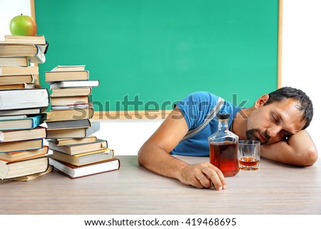 Drunk teacher fall asleep at classroom. Photo of adult man addicted to alcohol at the workplace, education concept - stock photo