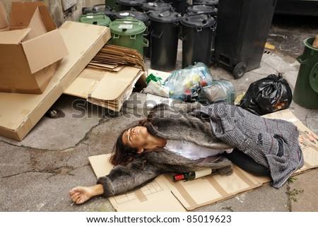 drunk tramp woman lying on cardboard in city trash area - stock photo