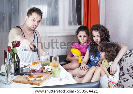 Drunk unshaven father watching TV with their children.