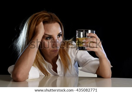 drunk woman alone in wasted and depressed face expression holding and looking thoughtful to scotch whiskey glass isolated on black background in alcohol abuse and alcoholic housewife concept