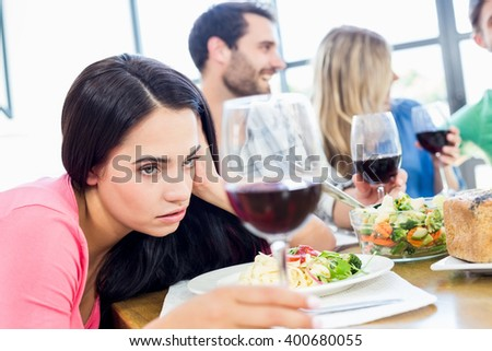 Drunk woman looking at wine glass while having meal with friends - stock photo