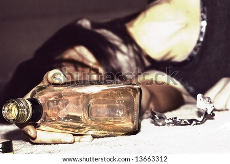 drunk woman lying on the floor, bottle of whiskey in the hand - stock photo
