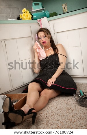 Drunk woman on kitchen floor crying and holding napkin - stock photo
