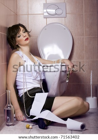Drunk woman sitting dizzy on the toilet floor - stock photo