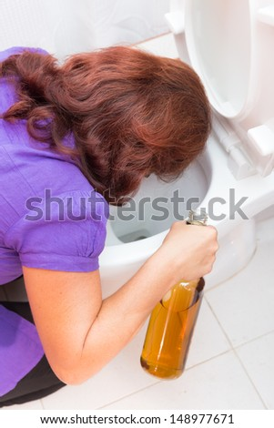 Drunk woman vomiting on a toilet bowl and holding a liquor bottle