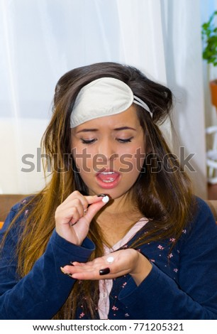 Drunk woman with a sleeping eye mak in her head, with a pill in her hand, hangover