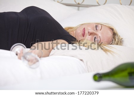 Drunk woman with glass, sleeping on bed - stock photo