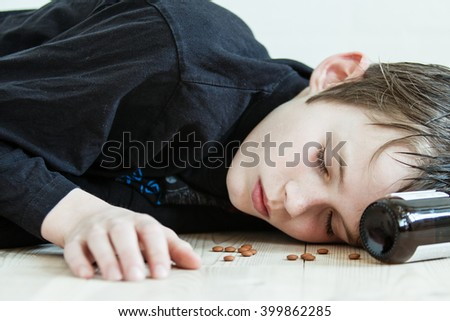 Drunk young boy sleeping it off after a party collapsed on the floor with a bottle at his head and nuts strewn around his face - stock photo