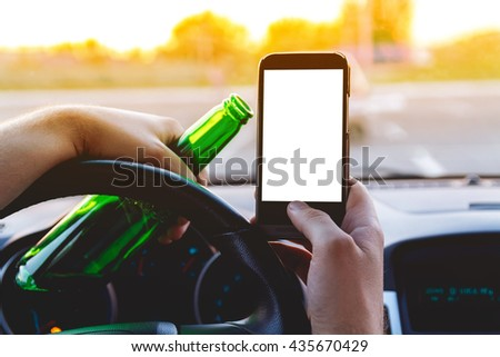 Drunk young man driving a car with a bottle of beer and mobile phone. Don't drink and drive concept. Don't text and drive. Driving under the influence (DUI), Driving while intoxicated (DWI) - stock photo