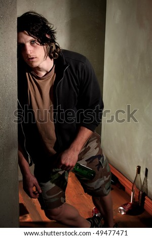Drunk young man leaning on a wall with beer bottle - stock photo
