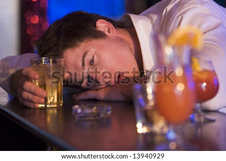 Drunk young man resting head on bar counter - stock photo