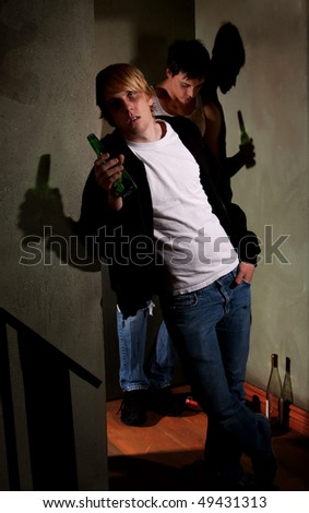 Drunk young men in hallway with bottles - stock photo