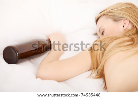Drunk young topless woman sleeping on bed with bottle of vine in hand. Isolated on white