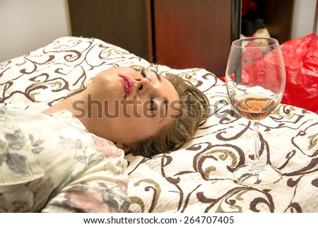 Drunk young woman falls asleep in bed near the glass of red wine. - stock photo