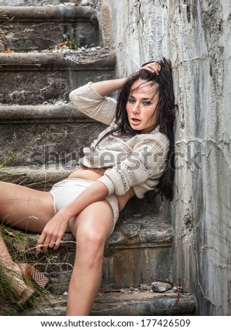 Drunk young woman lying on the stairs - stock photo