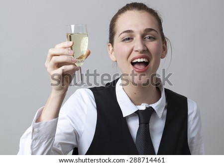 drunk young woman wearing uniform of wine waitress raising bubbly wine in glass of Champagne - stock photo