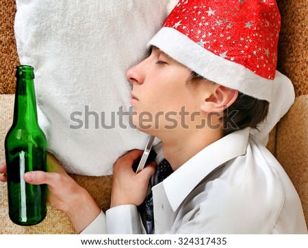 Drunken Young Man sleep in Santa Hat and Bottle of the Beer on the Sofa closeup