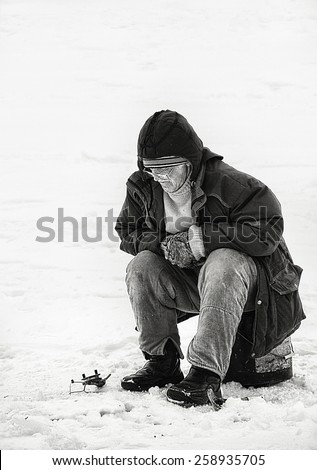DRUSKININKAI, LITHUANIA - december 9: traditional winter occupation in Lithuania on Dec 9, 2007. Fisherman fishing on ice in winter background. Black and white photo. Cold winter in Lithuania