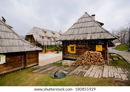 DRVENGRAD, SERBIA - DEC 30: Cat sit on a street of wooden houses village in serbian mountains on December 30, 2013 in Mecavnic. Traditional style village built by  Serbian film director Emir Kusturica - stock photo