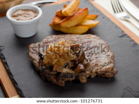 Dry Aged Hereford Rib-Eye Steak with Caramelised onions, Mixed Forrest Mushrooms, Pepper Sauce - stock photo