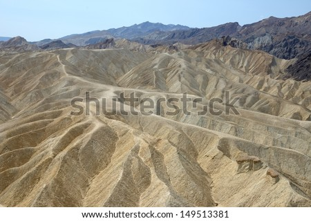 Dry, arid hills with ridges and gorges on s a sunny day at Zabriskie point, Death Valley,California, USA