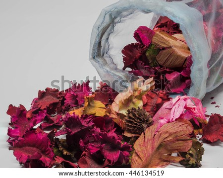dry aromatic flowers and spices spilling out of a bag onto a white background - stock photo