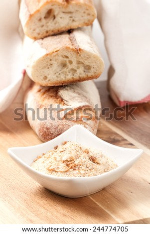 dry baguettes and bread crumbs on wooden table  - stock photo