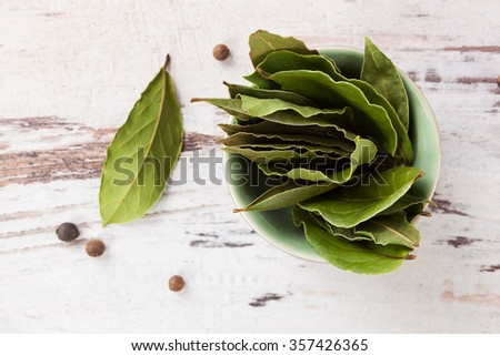 Dry bay leaves on white wooden textured background. Culinary herb, cooking ingredient and medical herb.  - stock photo