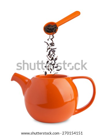 dry black tea falling from a spoon into  teapot isolated on white - stock photo