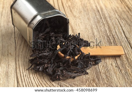Dry black tea large leaf Chinese in a metal can and near on wooden background