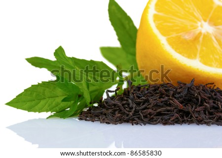 dry black tea leaves, lemon and mint isolated on white