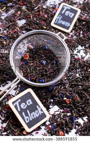 Dry black tea with flower petals. Selective focus. - stock photo