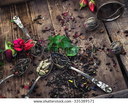 Dry brew tea in vintage and spoons on wooden background - stock photo