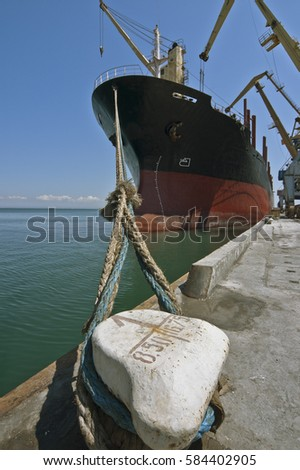 Dry cargo ship staying under loading operations at berth fixed with ropes