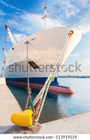 Dry cargo ship with bulbous bow moored in port - stock photo