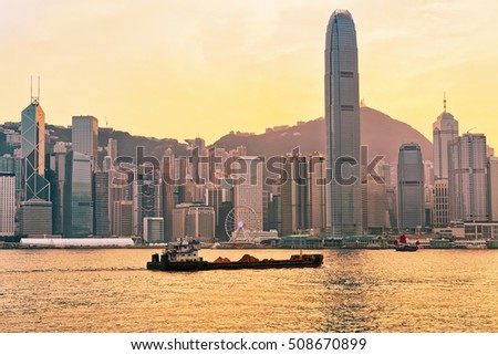 Dry cargo vessel and Victoria Harbor of Hong Kong at sunset. View from Kowloon on HK Island.