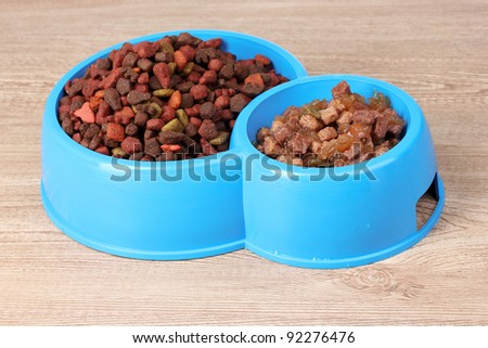 Dry cat food in bowls on wooden background - stock photo