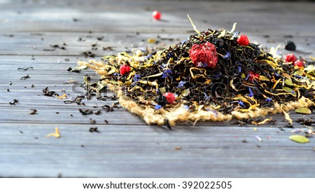 Dry Ceylon tea with berries - blueberries, raspberries, blackberries on a dark table closeup - stock photo