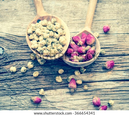 Dry chamomile and rose tea on a wooden spoons/toned photo - stock photo