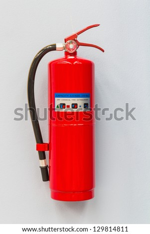 Dry chemical fire extinguisher on factory wall - stock photo