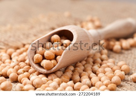 Dry chickpeas healthy nutrition food in wooden spoon on vintage textile background. Side view - stock photo