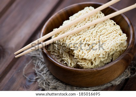 Dry chinese noodles with chopsticks in a wooden bowl, close-up - stock photo
