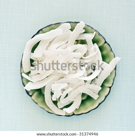 dry coconut flakes on a ceramic plate - stock photo