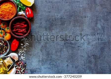 Dry colorful spices in bowls with fresh seasoning and healthy vegetables on dark rustic background, top view, border. Vegetarian or diet food concept - stock photo