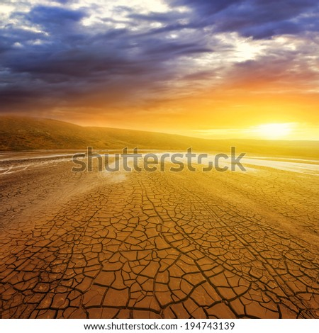 dry cracked earth at the sunset - stock photo