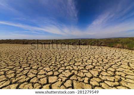 Dry cracked earth under the blue sky. Drought. - stock photo
