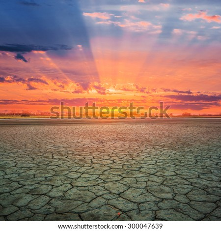dry cracked land at the sunset - stock photo