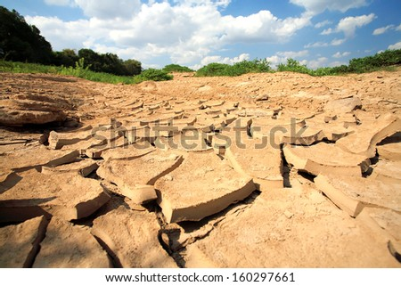 Dry cracked soil texture and blue sky. - stock photo