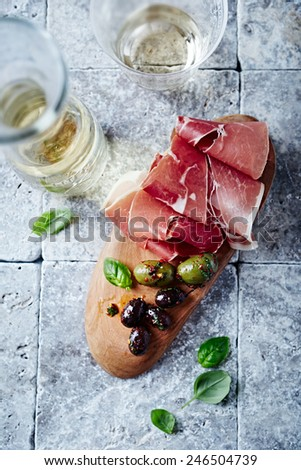 Dry cured ham, marinated olives and white wine (seen from above) - stock photo