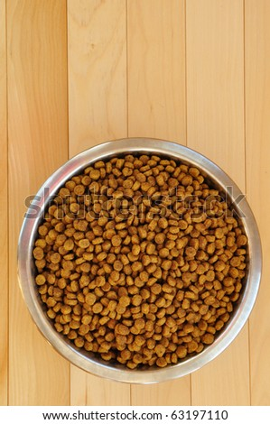 Dry Dog Food in a Stainless Steel Bowl on Hardword Floor - stock photo